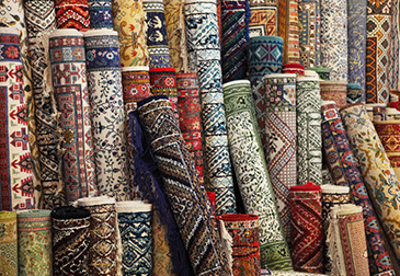 A bunch of rugs rolled up and stacked together
